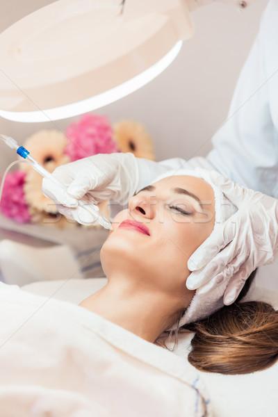 Beautiful woman relaxing during non-invasive facial treatment Stock photo © Kzenon