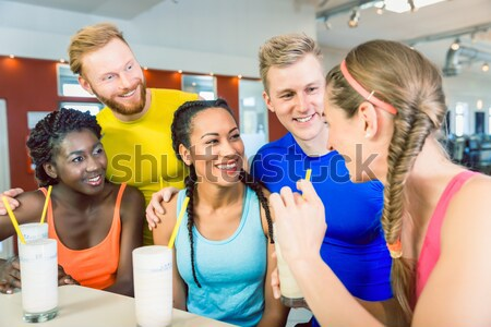 Multi-ethnic group of cheerful friends drinking protein shakes Stock photo © Kzenon