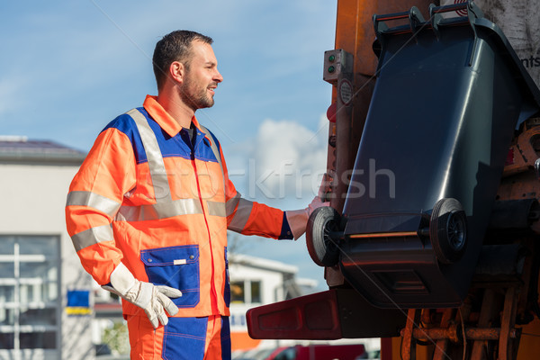 Garbage collection worker putting bin into waste truck Stock photo © Kzenon