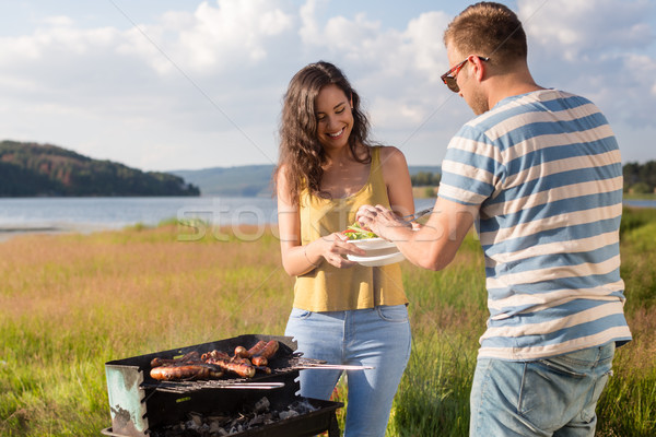 Man and woman having barbecue at lakeside in nature Stock photo © Kzenon