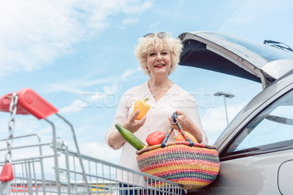 Cheerful senior woman holding a basket full of fresh vegetables  Stock photo © Kzenon