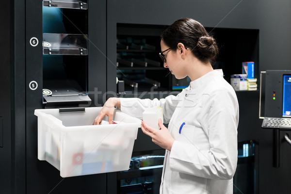 Pharmacist choosing the best medicines during work in drugstore  Stock photo © Kzenon