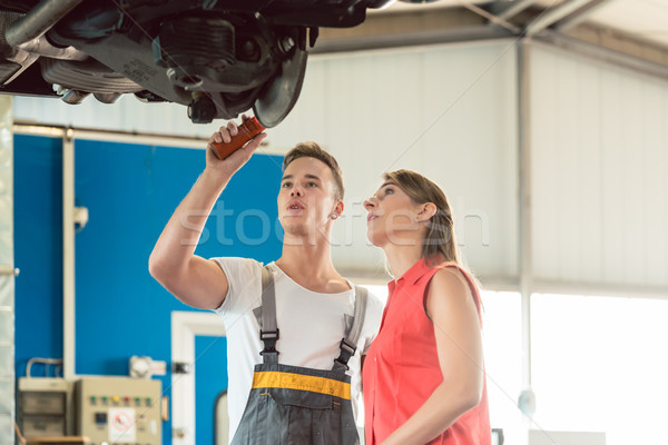 Stock photo: Auto mechanic checking the disk brake rotors of the car of a female customer