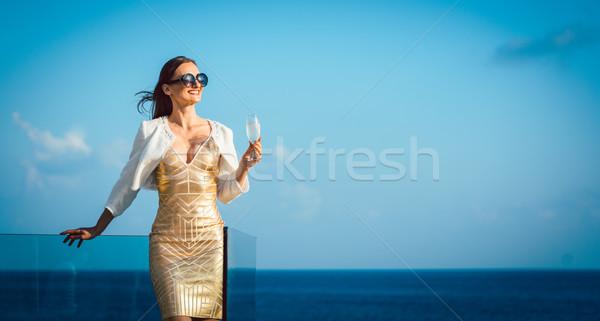 Woman drinking sparkling wine looking over ocean Stock photo © Kzenon