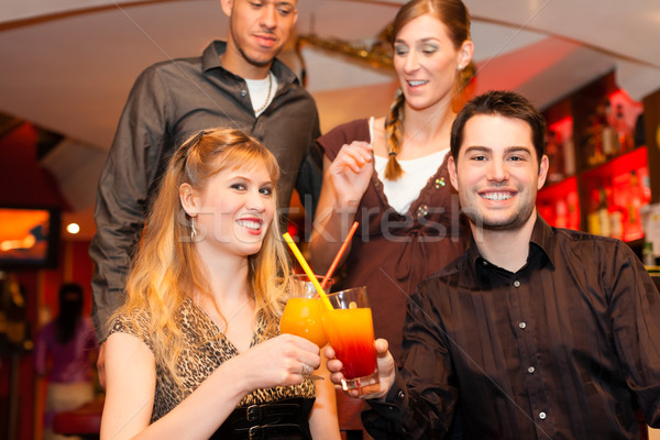 Stock photo: Young couple drinking cocktails in bar or restaurant