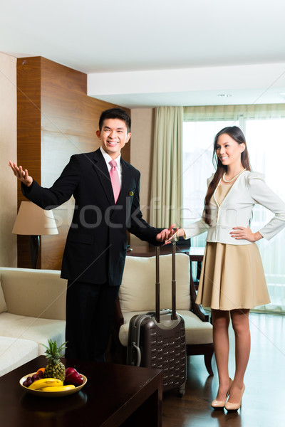 Asian Chinese hotel manager presenting suite Stock photo © Kzenon