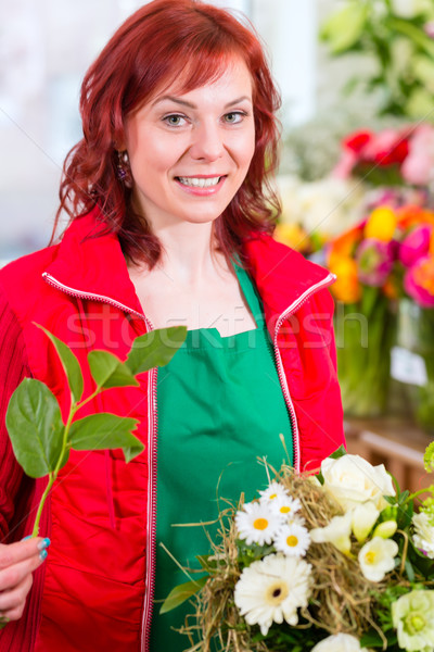 Florist binding flower bunch in shop  Stock photo © Kzenon