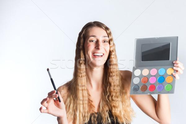 Woman putting make-up on Stock photo © Kzenon