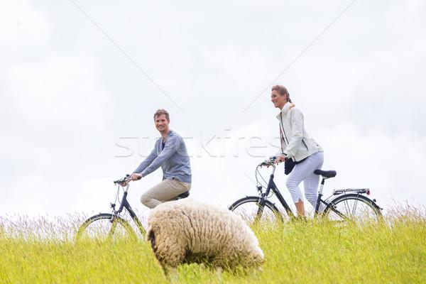 Couple having sea coast bicycle tour at levee Stock photo © Kzenon