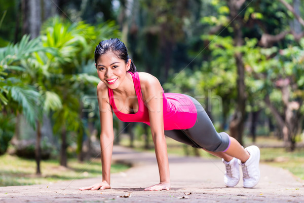 Strong Asian woman doing sport push-up in park Stock photo © Kzenon