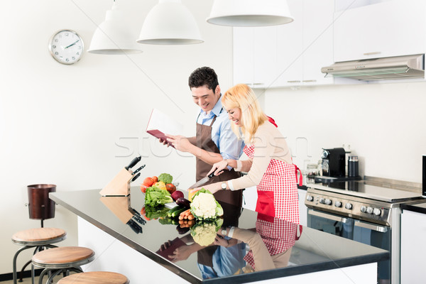 Asian couple cooking in stylish and modern kitchen Stock photo © Kzenon