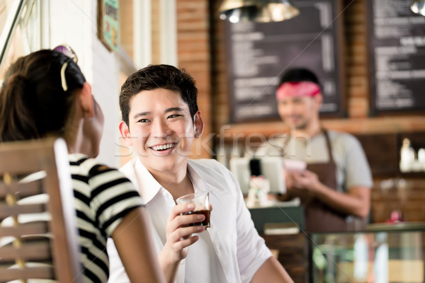 Asian couple in cafe flirting while drinking coffee Stock photo © Kzenon