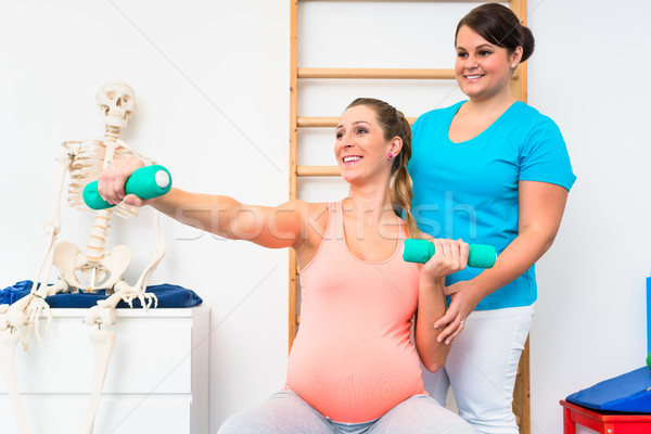 Pregnant woman working out with dumbbells in physical therapy Stock photo © Kzenon