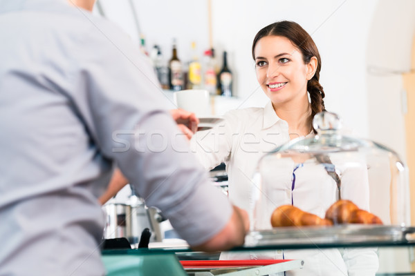 Beautiful waitress serving male customer with a cup of coffee fo Stock photo © Kzenon