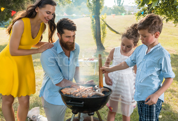 Father and son preparing meat on charcoal barbecue grill during  Stock photo © Kzenon