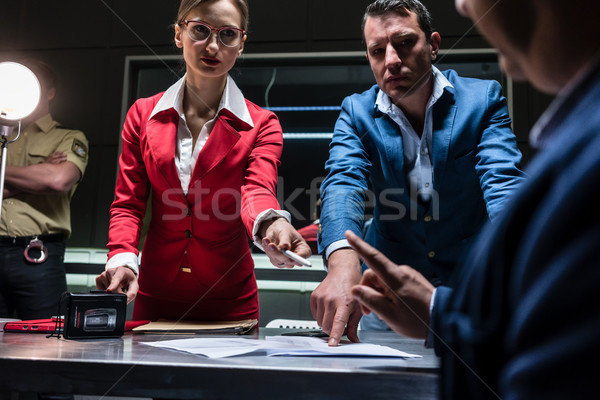 Stock photo: Two persuasive investigators trying to obtain a confession from