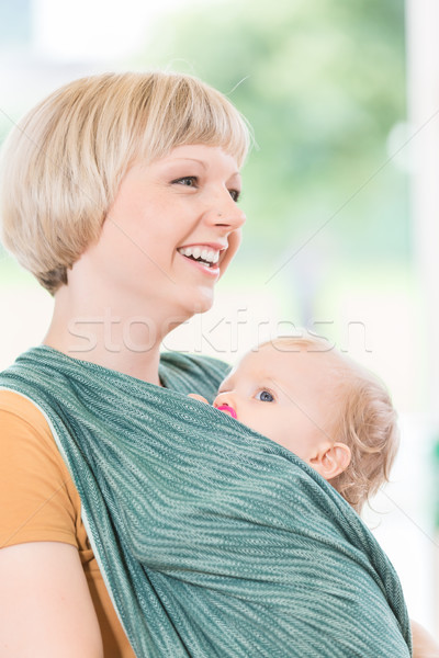 Young mum with child in baby sling for better mother-child bondi Stock photo © Kzenon