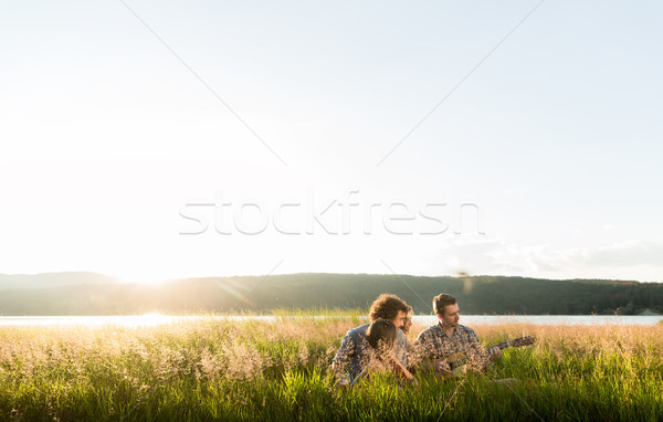 Group of young people in sundown playing guitar music Stock photo © Kzenon