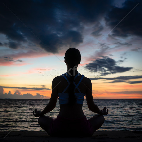 Fit woman sitting in lotus position while practicing yoga on the beach Stock photo © Kzenon