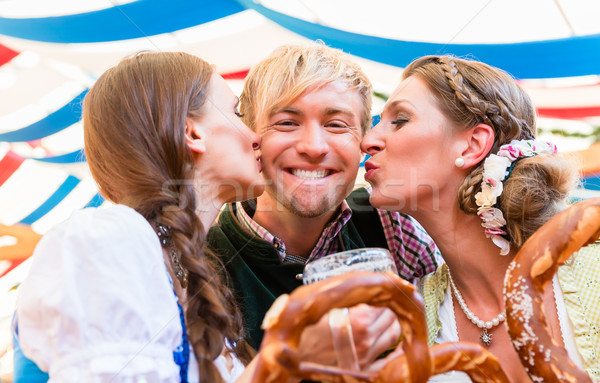 Two women kissing man at Bavarian beer tent Stock photo © Kzenon