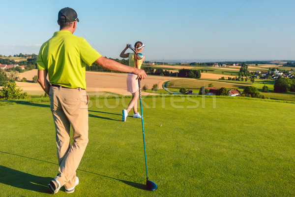 Man watching his partner striking the ball during match on the golf course Stock photo © Kzenon