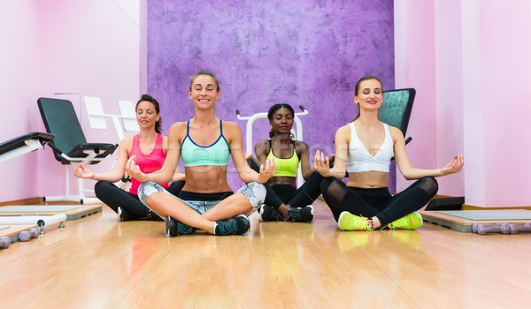 women sitting in lotus position as relaxing exercise in fitness club Stock photo © Kzenon