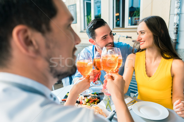Four friends toasting together with a cold refreshing alcoholic drink Stock photo © Kzenon