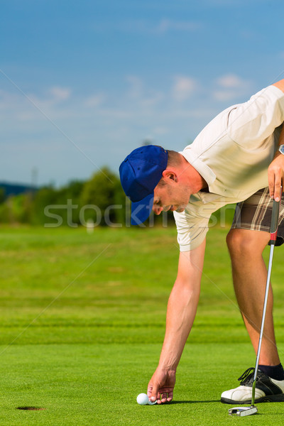 Young golf player on course putting Stock photo © Kzenon
