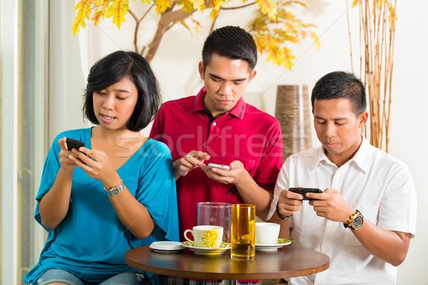 ázsiai emberek szórakozás mobiltelefon együtt iszik Stock fotó © Kzenon