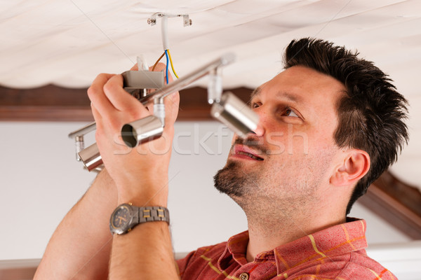 Worker is installing a luster Stock photo © Kzenon
