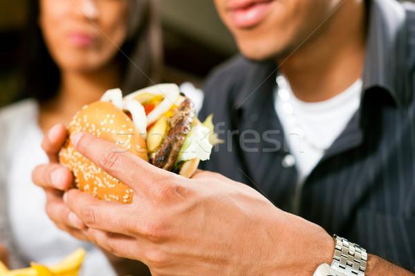 Man restaurant eten hamburger gelukkig afro-amerikaanse Stockfoto © Kzenon