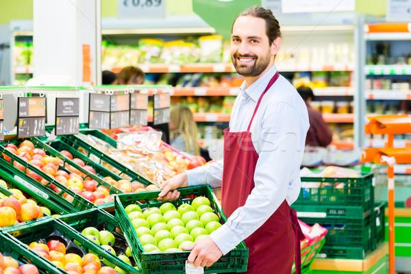 Hypermarket clerk filling up storage racks Stock photo © Kzenon