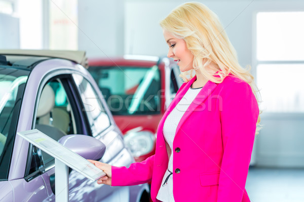 Woman choosing car for buying in dealership  Stock photo © Kzenon