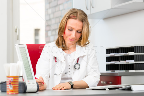 Young female doctor sitting in surgery at desk Stock photo © Kzenon