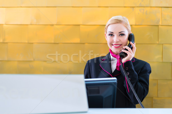 Hotel receptionist with phone on front desk Stock photo © Kzenon