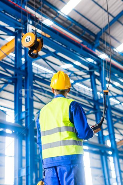 Worker in factory controlling crane with remote Stock photo © Kzenon