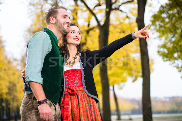 Man and woman in Bavarian Tracht, girl pointing  Stock photo © Kzenon
