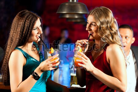 Girls enjoying nightlife in a club, drinking cocktails  Stock photo © Kzenon