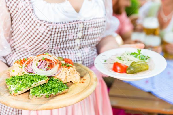 Waitress serving Bavarian food in beer garden Stock photo © Kzenon