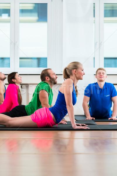 Recreational athletes doing yoga exercises in fitness gym Stock photo © Kzenon