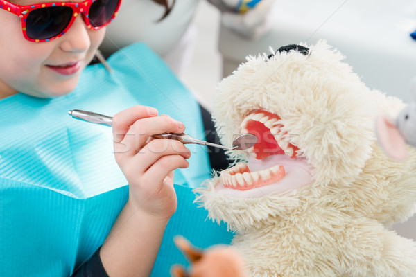 Child at dentist office looking after teeth of pet toy Stock photo © Kzenon