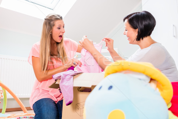 Pregnant woman and friend sharing baby clothes Stock photo © Kzenon