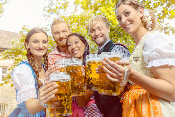 Friends in beer garden with beer glasses Stock photo © Kzenon