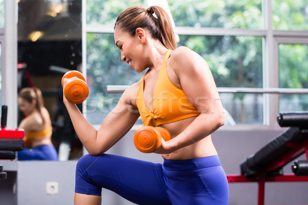 Young Asian woman doing bodybuilding with dumbbells Stock photo © Kzenon