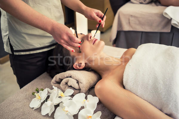 Stock photo: Relaxed woman lying down on massage bed during facial treatment