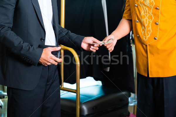 Midsection view of man giving tip in hotel Stock photo © Kzenon