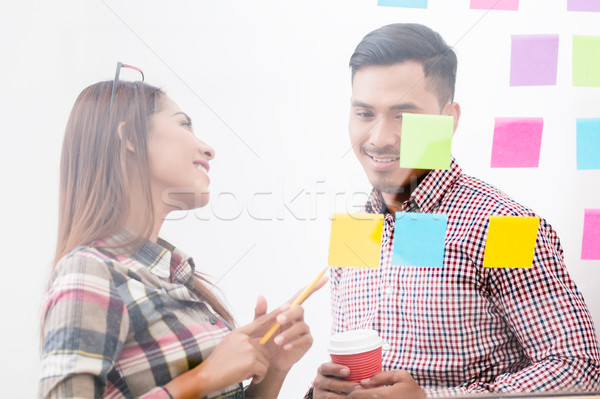 Experienced woman helping her colleague with tasks Stock photo © Kzenon