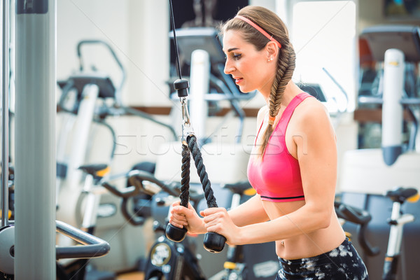Happy fit woman wearing pink fitness bra while exercising with cable rope Stock photo © Kzenon