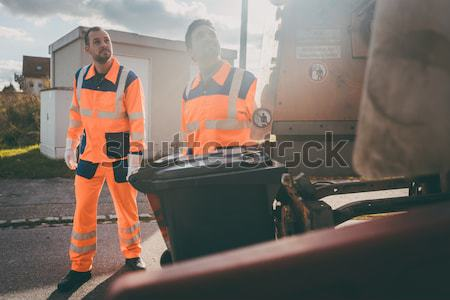 Two refuse collection workers loading garbage into waste truck Stock photo © Kzenon