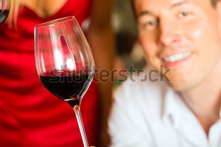 Couple drinking red wine clinking glasses Stock photo © Kzenon